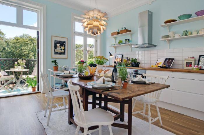 peinture murale bleu ciel dans cuisine au carrelage blanc meuble cuisine blanc avec plan de travail bois table bois brut et chaises boisées