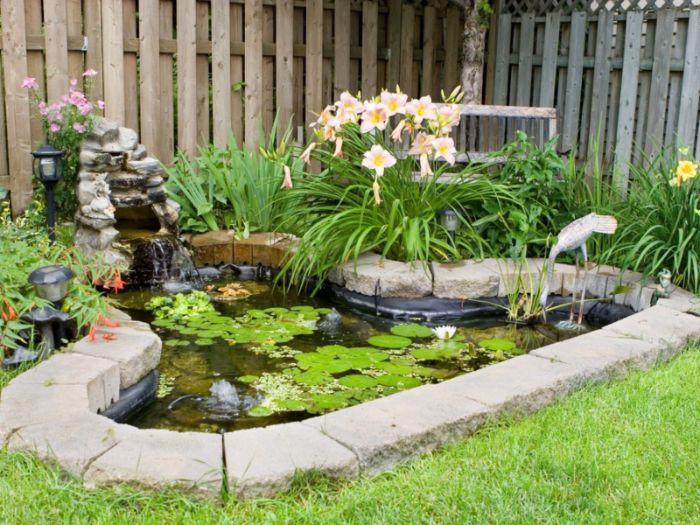 petit bassin de jardin naturel style jardin zen entouré de végétation et avec nympheas cloture de bois gazon vert