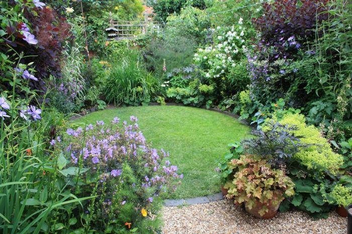 petit gazon forme ronde avec bordure en dalles de pierre revetement gravier plantes vertes et arbustes aux alentours