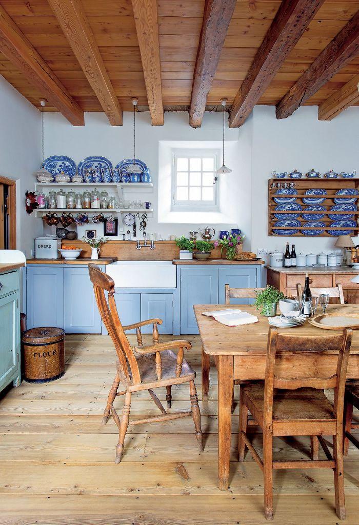 petit vaisselier mural plafond poutres chaises et table salle à manger de bois façade cuisine couleur bleue murs blancs