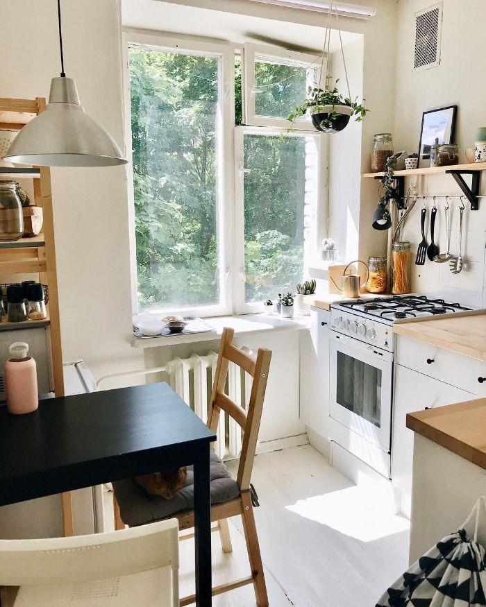 petite cuisine en l blanche avec des plans de travail noirs table salle à manger noire plantes suspendues