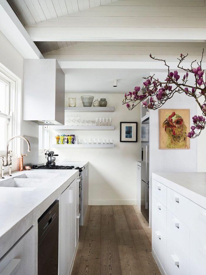 petite cuisine en longueur en blanche avec des etageres au mur et une branche aux fleurs violets