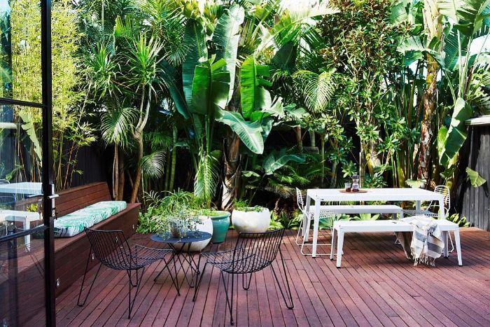 petite terrasse aménagée avec mur végétal table chaises et banc blanc table et chaise en métal plante en pot