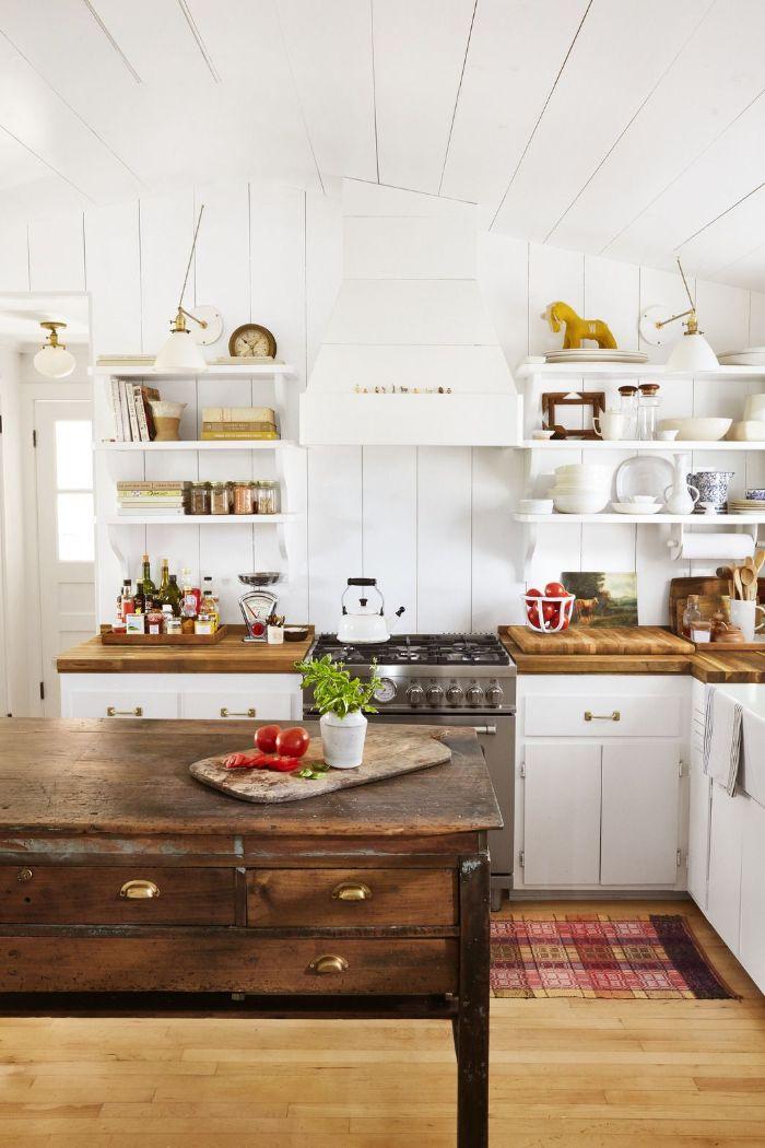 plan de travail et ilot central bois brut murs et plafond poutres de bois blanches parquet bois clair façade0cuisine blanche