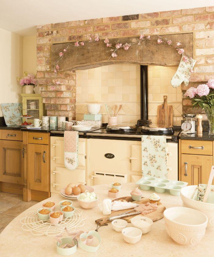 poêle ancien façade cuisine bois clair crédence carrelage beige mur de briques plan de travail noir table pâtissière
