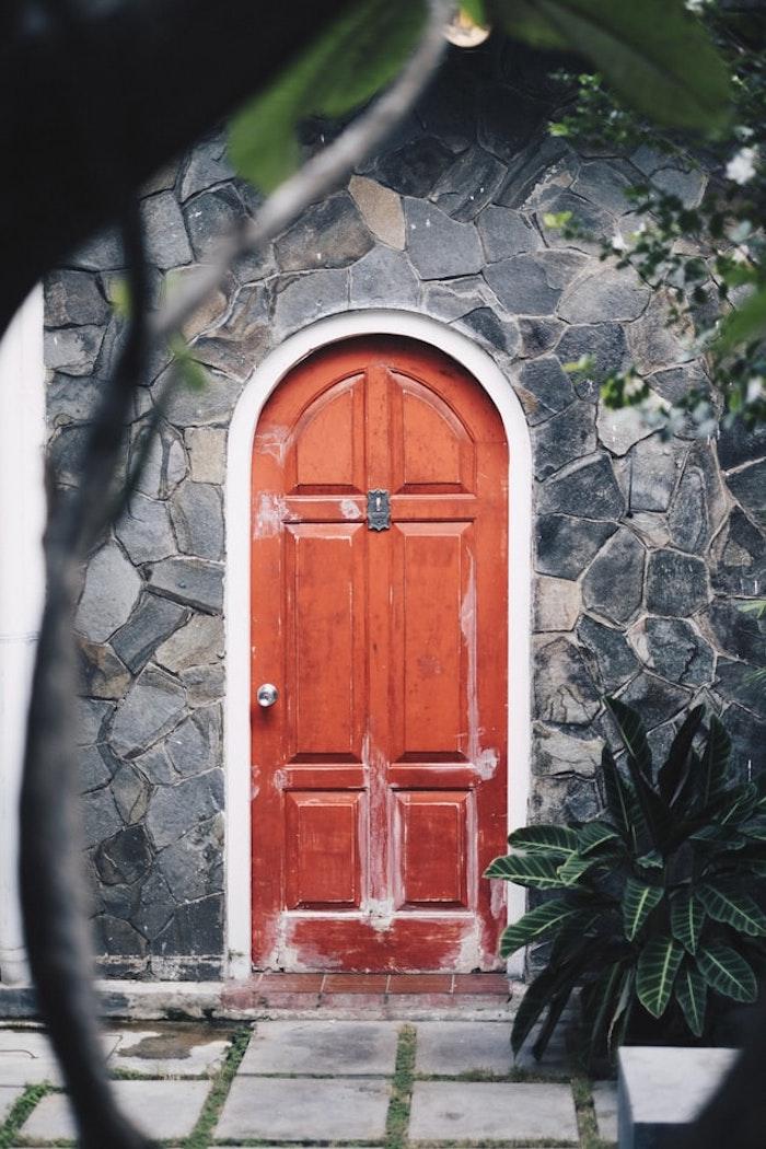 porte d entree rouge forme ovale maison en pierres