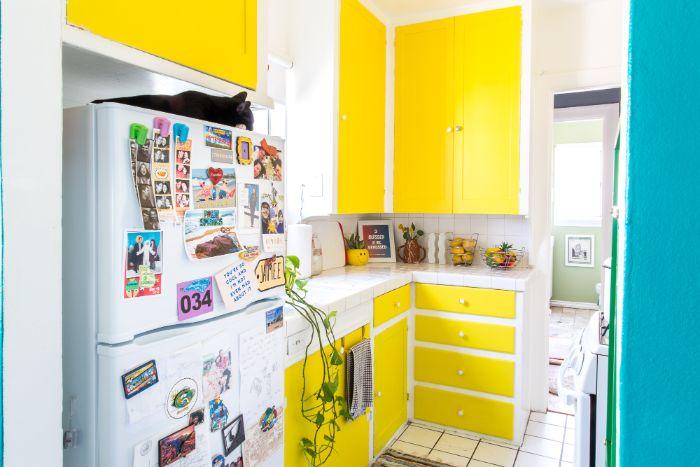portes placards et tiroirs de cuisine repeintes de couleur jaune vitamintée plans de travail blancs frigo blanc cuisine petit espace design