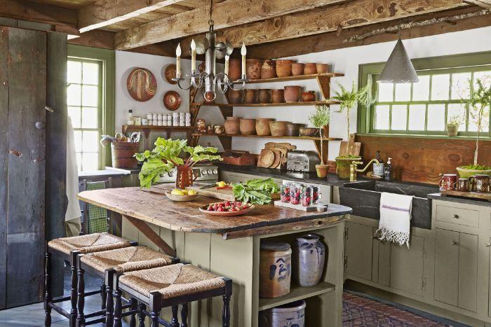poutres apparentes de bois dans une cuisine campagne avec des étagères de bois ouvertes ilot central bois chaises bar bois tapis coloré