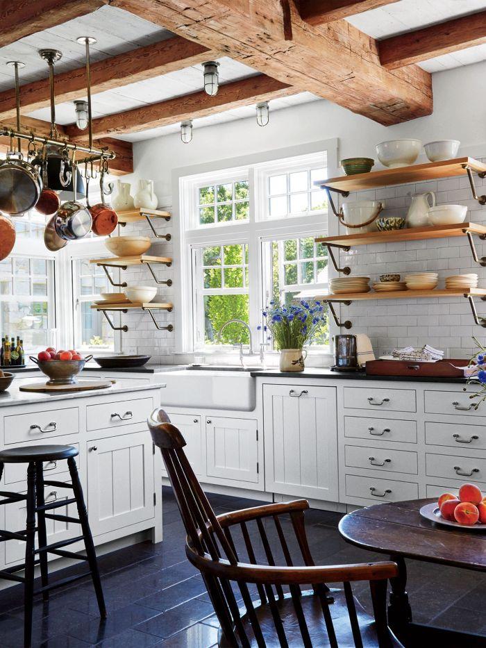 poutres apparentes de bois mur carrelage blanc façade cuisine blanche sol carrelage noir chaise et table bois ilot central blanc