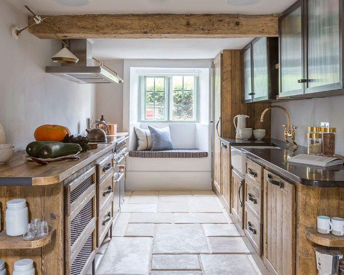 poutres apparentes meuble cuisine bois brut bas sol en dalles de pierre petite fenêtre murs blancs cuisine sous sol