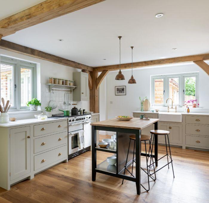 poutres bois apparentes dans une cuisine bois peinte en gris clair plans de travail bois parquet bois ilot table bois et métal