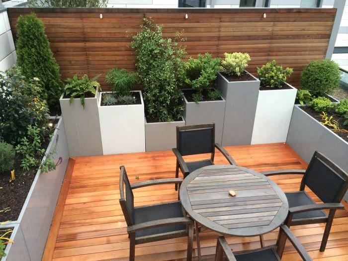 quel aménagement extérieur terrasse habillée de bois avec table ronde bois et chaises jardin brise vue bois et jardinièrs avec plantes vertes