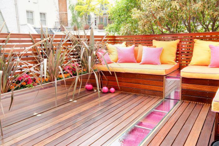 quel amenagement petites terrasse de bois avec assise bois coussins colorés rose et jaune bordure fleuri