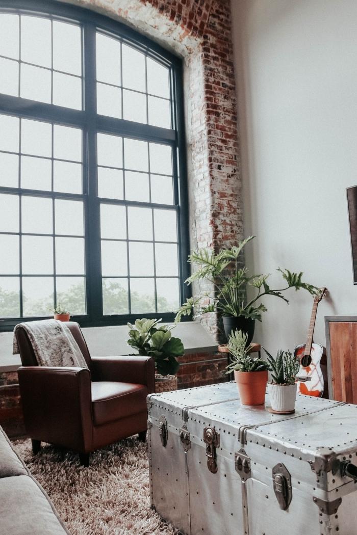 rêvetement mural briques rouge tapis moelleux marron deco salon industriel vintage table coffre vintage