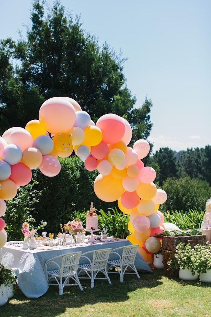 reception dans le jaridn pendant les paques un arc en ballons au desuss d une table couvert de nappe blanche