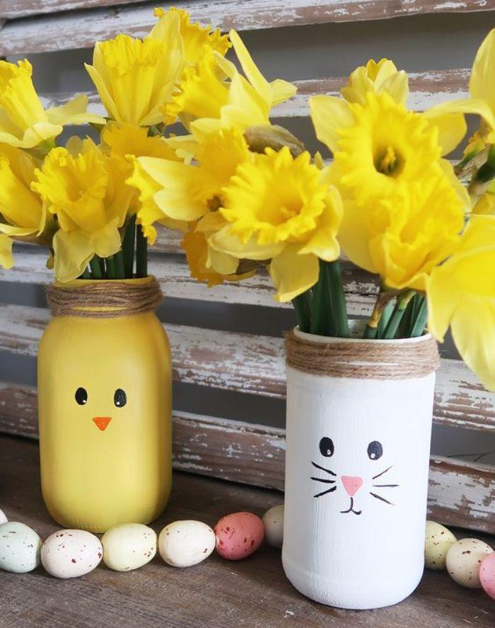 recycler des pots en verre pour fabriquer une idee deco paques pots peints motif lapin et poussin avec ficelle autour du col et des fleurs à l intérieur