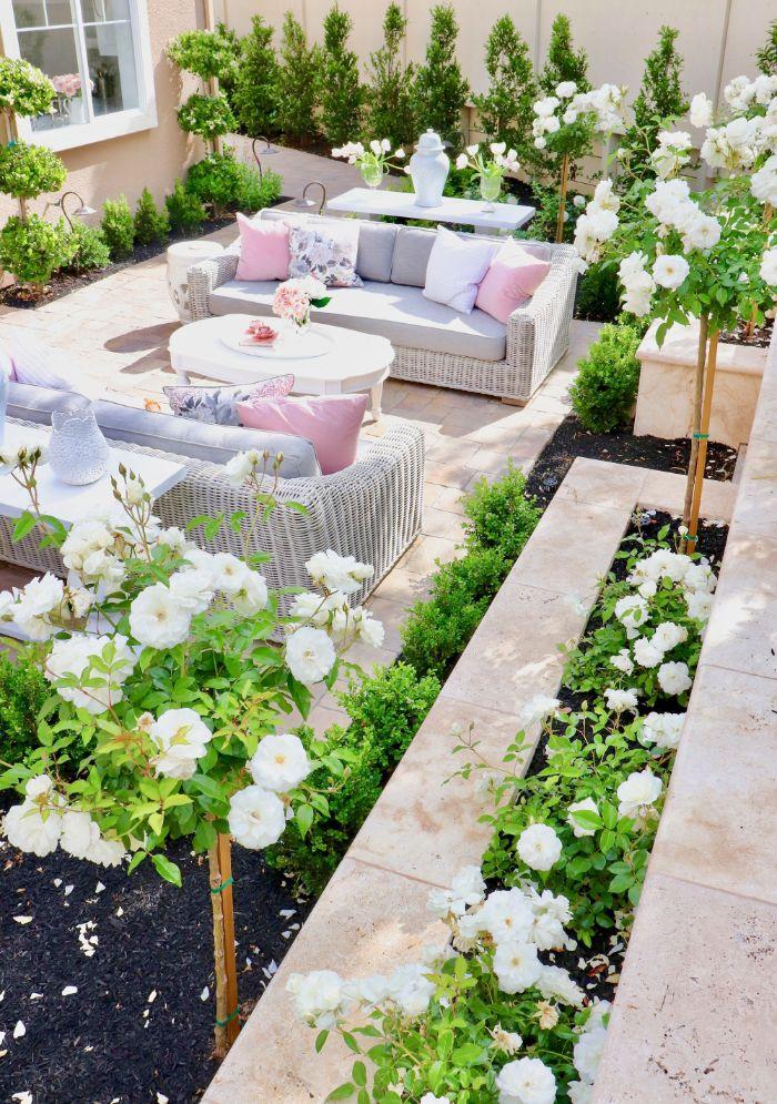 salon de jardin cocooning en résine tressée au milieu d un jardin entourée de plantes en bordure fleurs blanches