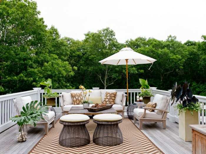 salon de terrasse en bois avec des coissins d assise gris tables orientaux deco boisée et plantes parasol terrasse aménagée