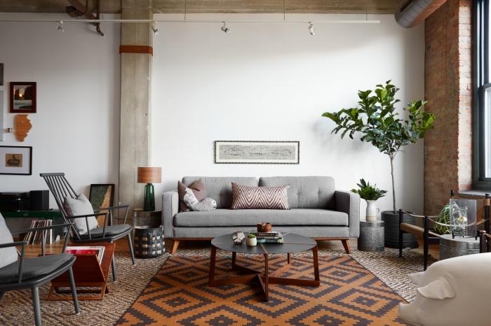 salon style industriel colonne béton chaise gris anthracite canapé gris clair mur de cadres plantes