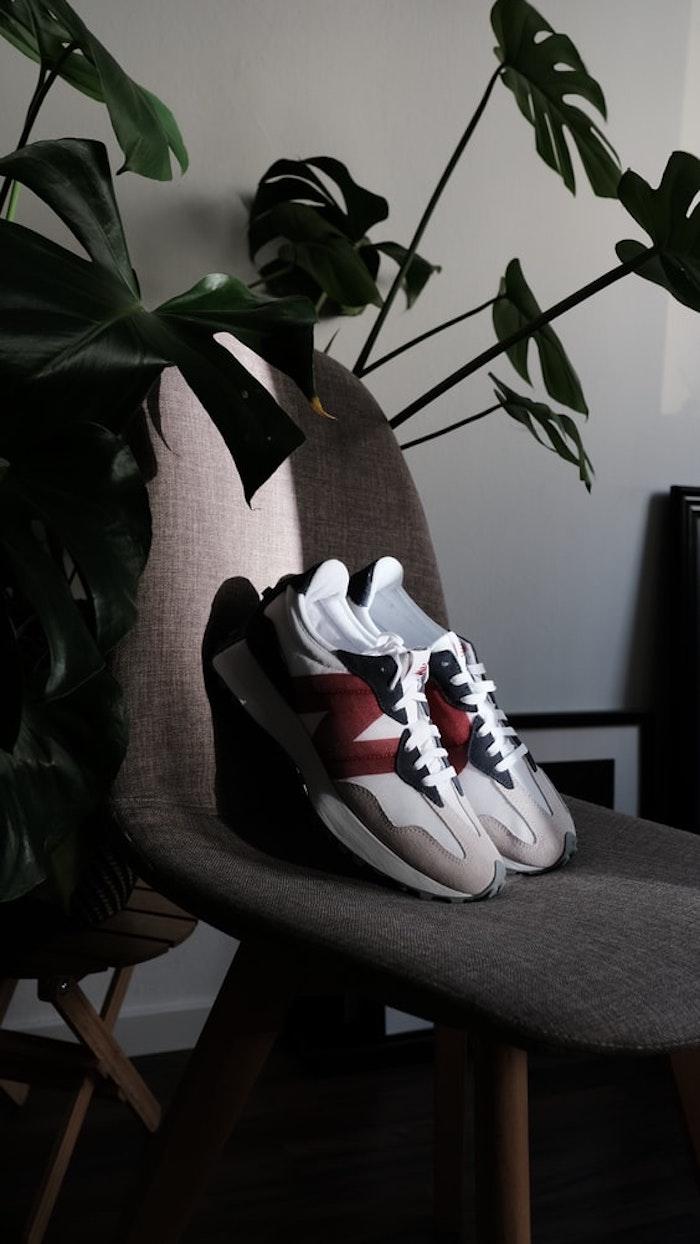 sneakers new balance sur une chaise scandinave couleur gris plante verte d interieur