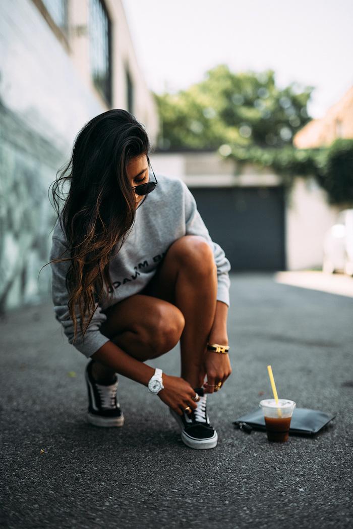 streetwear femme qui combine des sneakers vans un pull spotrif et des short noir