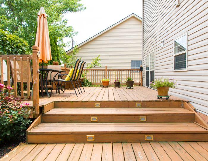 table et chaises en métal sur terrasse élevée adossé à une maison plantes en pot terrasse aménagée extérieure
