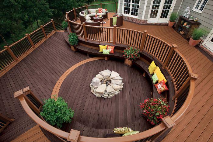terrasse en bois composite avec un banc rond chargé de coussins et cheminée au milieu maison bois grise
