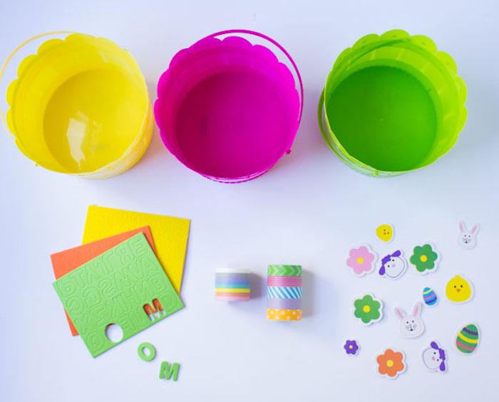 trois paniers en plastique et couleurs différentes des papiers multicolres et des autocollants fabriquer panier paques