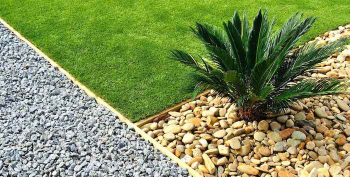 trois surfaceces differentes divisées du gazon du gravier et des galets autour d une petite palme