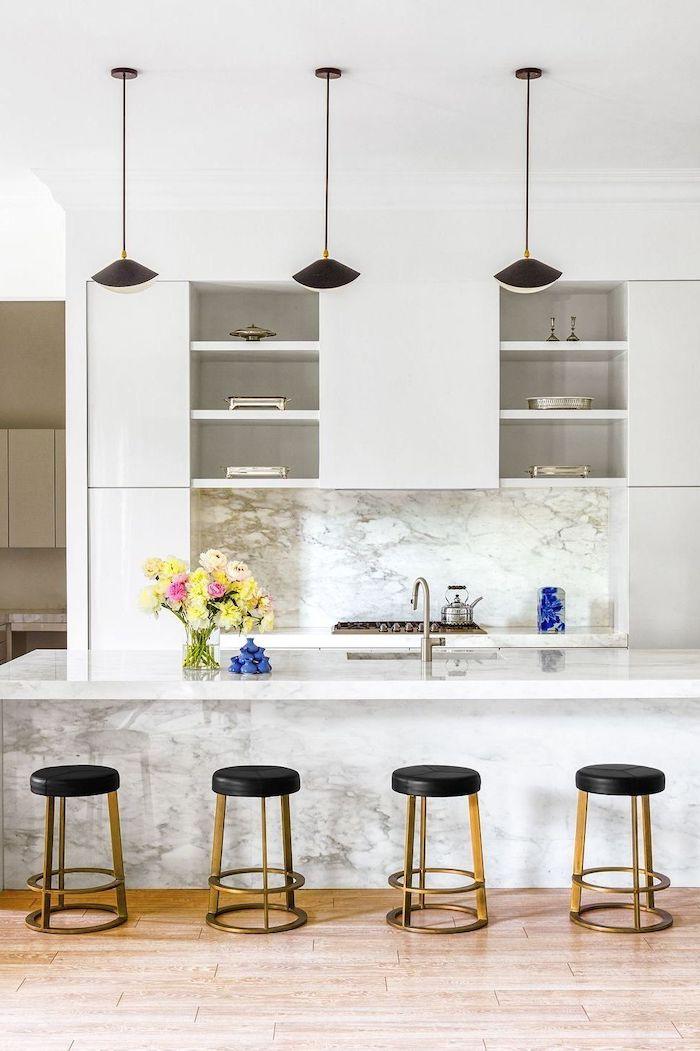 un aménagement moderne petite cuisine avecdes surfaces en marbre lapes pendantes et bar chaises