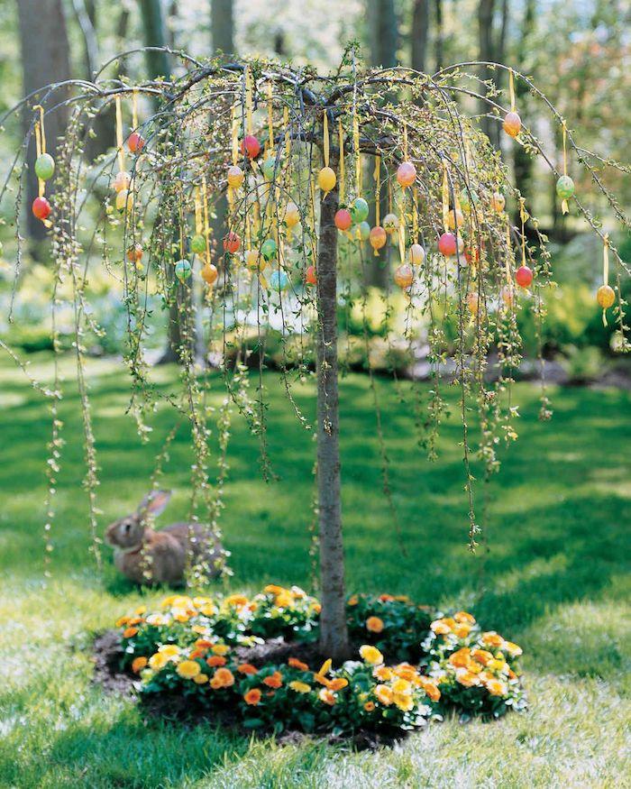 un arbre dans le jardin avec des oeufs multicolorés accrochées un lapin dans l herbe en arrière