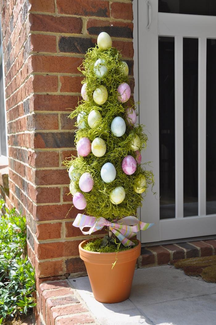 un arbre en pot a fleur devant la porte d entrée décorée des oeufs colores deco paques 2021