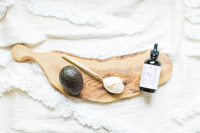 un avocat une cuillère d huile de coco et de lavande sur un plateau en bois pour masque capilaire maison