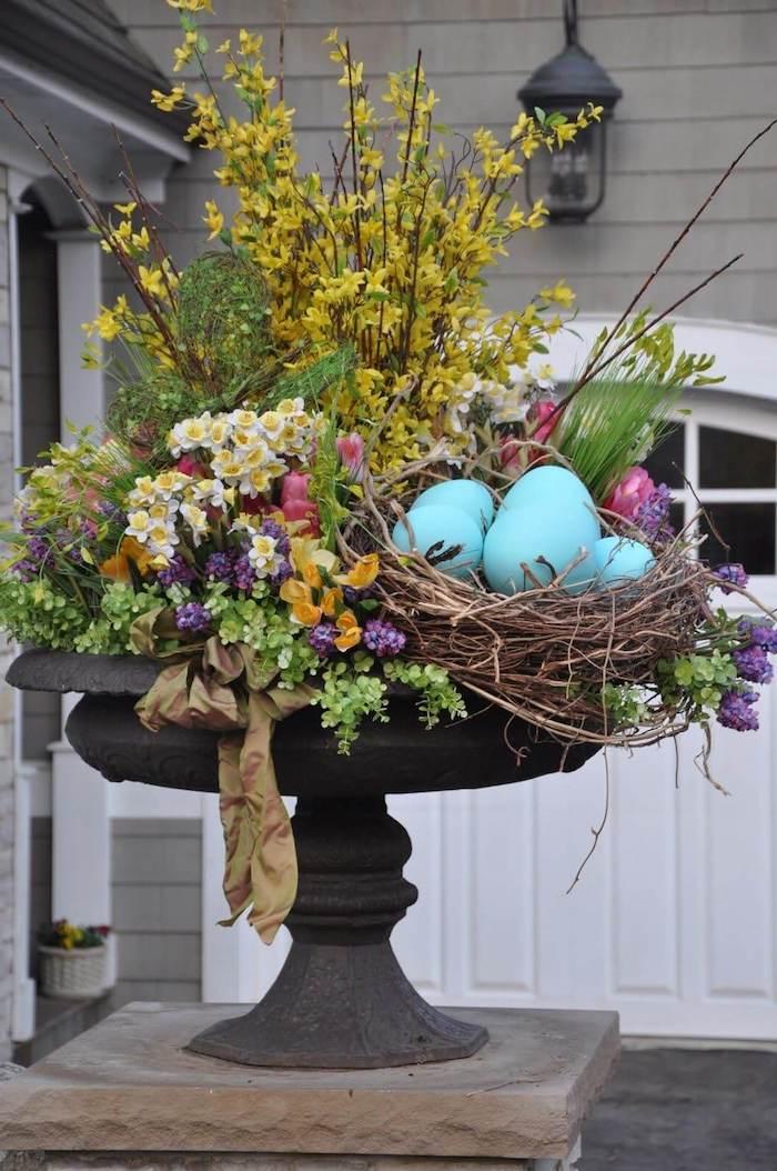 un cache pot en metal rempli des fleures printanieres et des oeufs decoratifs devant une maison