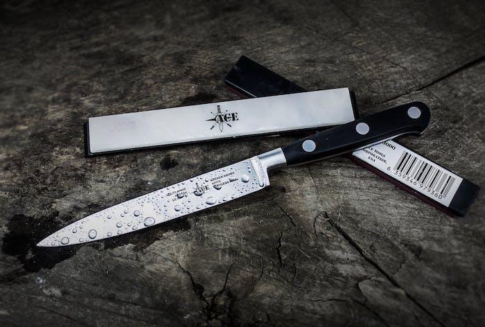 un couteau de cuisine original arosse des gouttes d eau sur une surface en bois