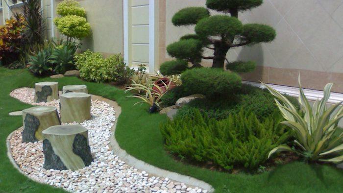 un espace vert devant maison avec des plantes diferents et création d un parterre avec galets