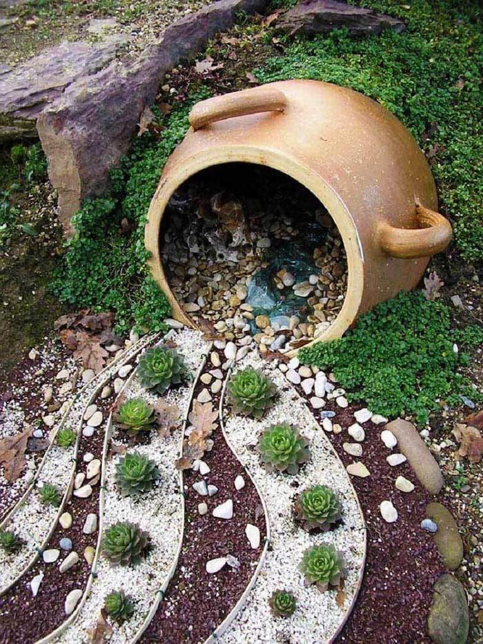 un grand pot de fleurs qui verse des pierres decoratifs autour des succulents jardin gravier decoratif