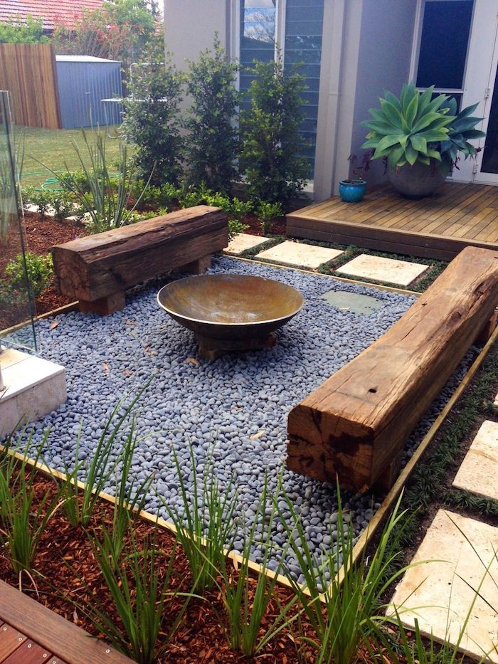 un jardin assemblé d un massif de fleurs avec des pierres entre des banc rustiques en bois
