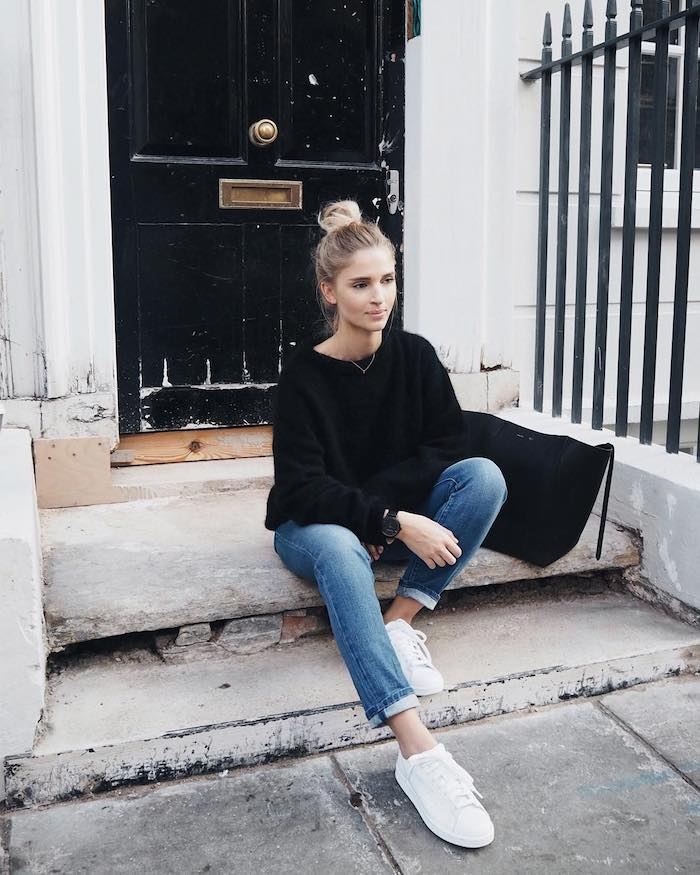 un look casual américain avec des jeans enroulé et un pull noir une fille assise devant une porte