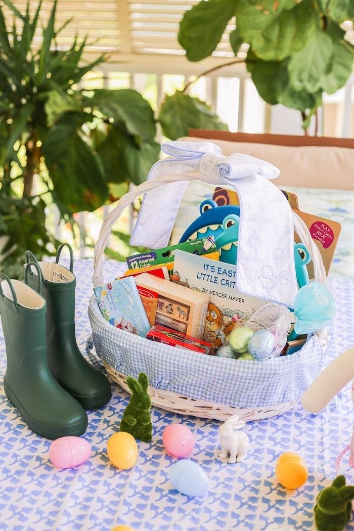 un panier de paques sur une nape rempli des cadeau des bottes en caoutchouc a coté