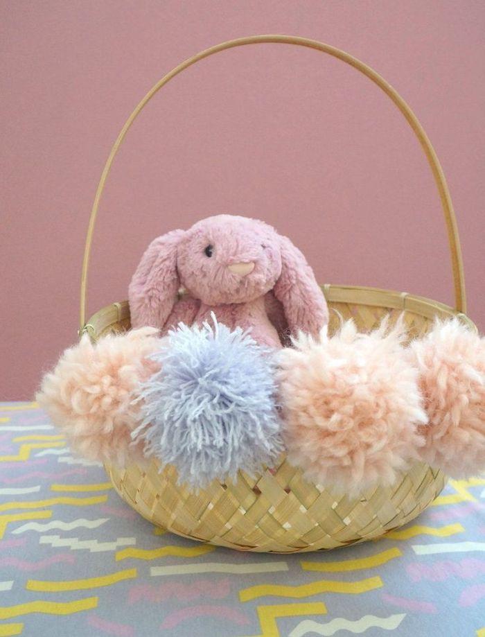 un panier en paille décoré avec des pompons et un lapin en pelouche mignon décoration de paques a fabriquer