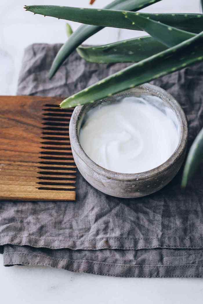 un peigne en bois sur une serviette laine a coté d un aloé et une tasse de masque cheveux secs