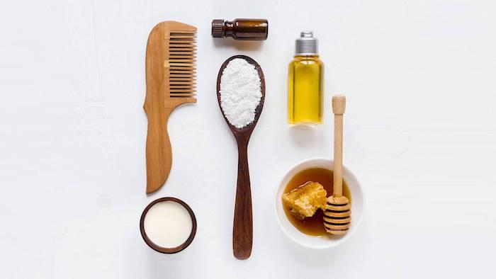 un peine et cuillère en boi avec huiles essentiels et une coupe de miel pour cehveux abîmés