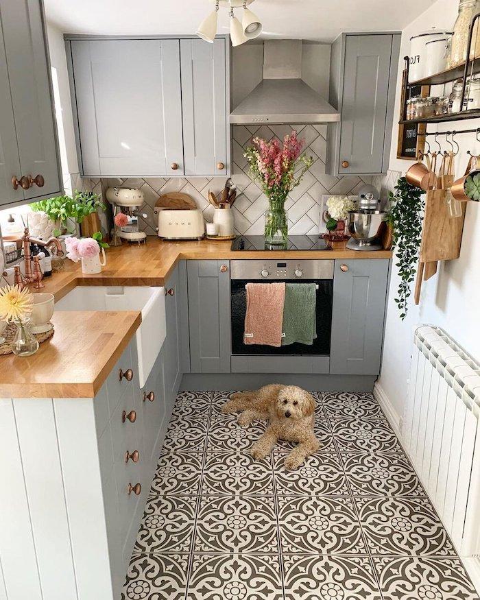 un petit chien allongé au sol avec carrelage a motifs noir et blancs idée d aménagement petite cuisine en u