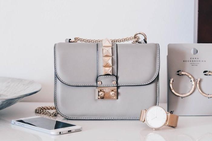 un sac a main avec des elements dorées et des cristaux a coté d un pair des bijoux et telephone portable