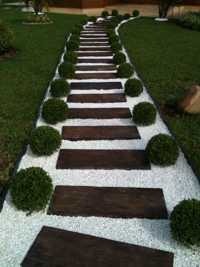 une allée vers la maison fait de galt blanc et des marchepieds en bois avec deux rangées des arbustes rondes