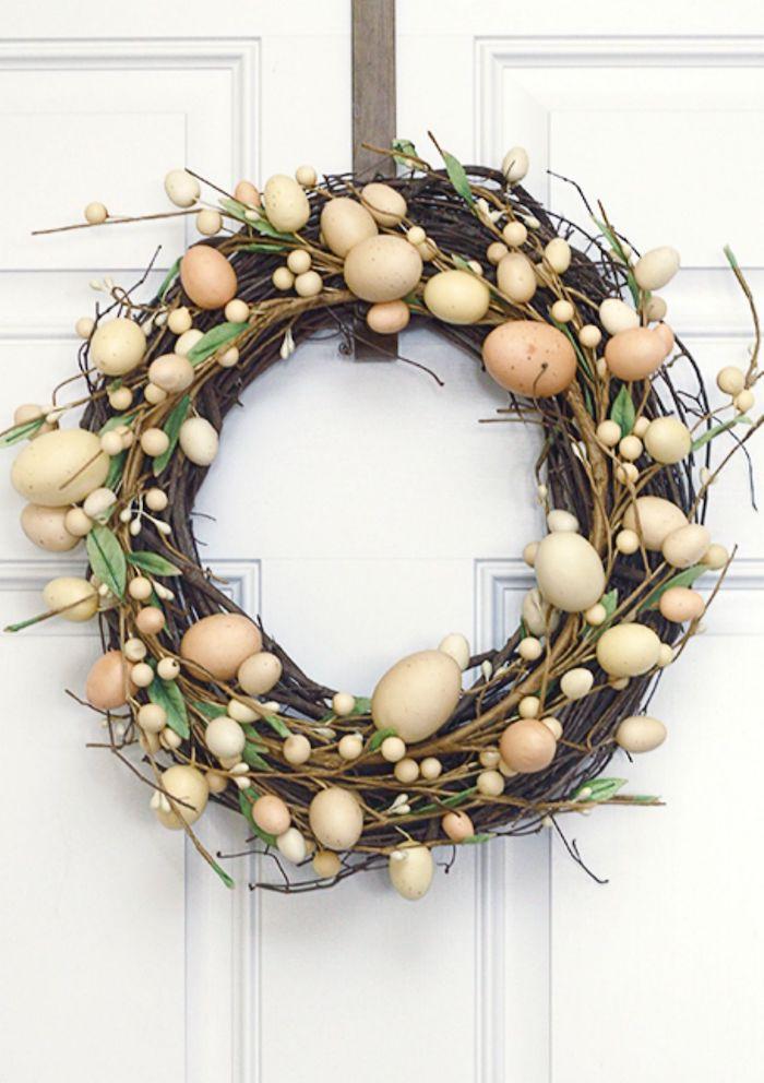 une couronne de paques elabore en brinsilles et des oeufs décoratifs accroché sur la porte d entrée blanche