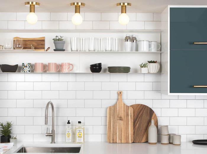 une crédence en carrelage blanc des lampes au plafond et des planche à découper dans une cuisine 10 m2
