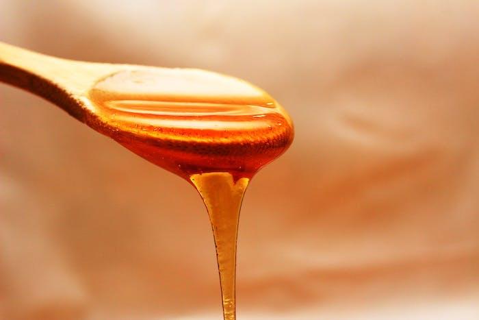 une cuillère en bois pleine de miel au fond orange