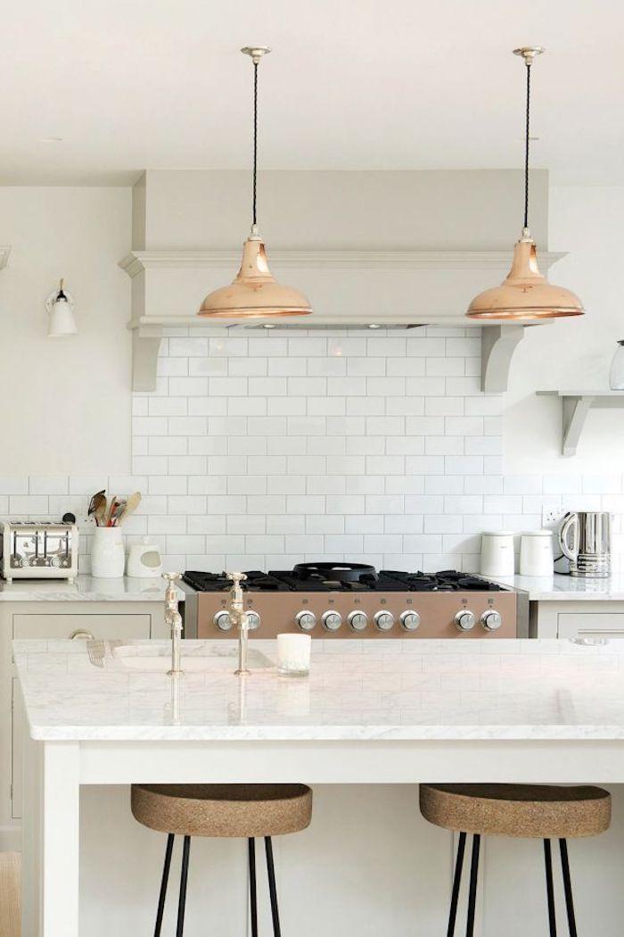 une cuisine blanche avec des lampes pendantes cuivrés et deux chaises hautes au dessous de la table